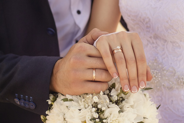 closeup-shot-newlyweds-holding-hands-showing-wedding-rings_181624-15865