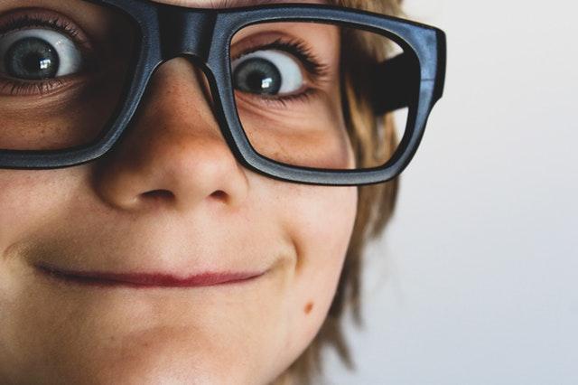 Detail na tvár chlapca s veľkými dioptrickými okuliarmi.jpg