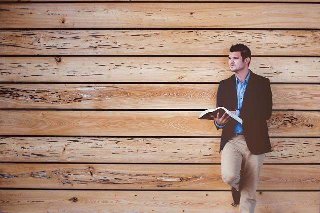 Muž s knihou v ruke stojí pri drevenej stene a pozerá do diaľky.jpg