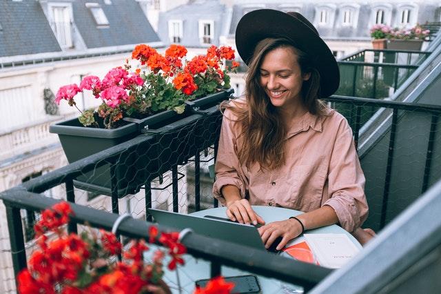 Žena v klobúku sedí na balkóne a pracuje s notebookom