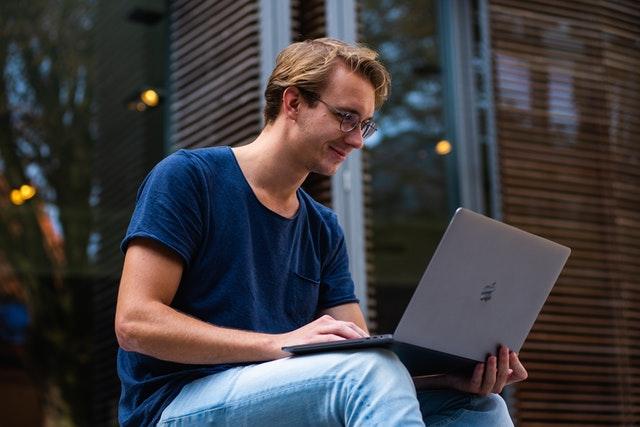 Chlapec v okuliaroch pozerá na počítač, ktorý drží v rukách